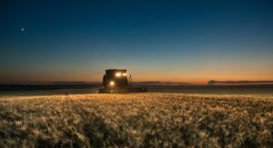 Photo of a tractor harvesting wheat at sunset